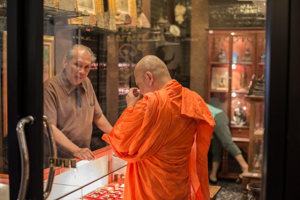 Buddhist Monk examining religious artifacts in Chatuchak